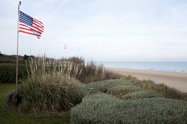 An American flag above Omaha Beach, one of the five landing sites along the Normandy coast where allied forces landed on D-Day, 6 June 1944, as Operation Overlord, the invasion of western Europe, was...