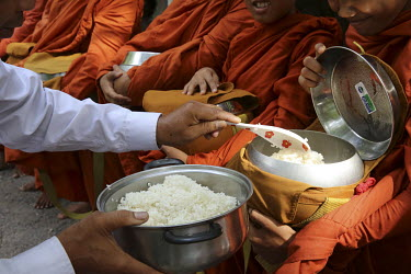 Monks receive alms (cooked rice) from local residents.