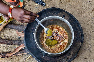 Yakawa Bawa Abacha cooks pasta on a small fire. Yakawa Bawa Abacha lives with her five children and her husband in an informal IDP camp in Diffa. She struggles to buy food for her children who often g...