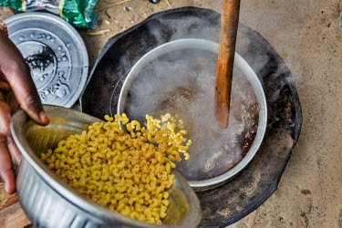 Yakawa Bawa Abacha cooks pasta on a small fire outside her camp. Yakawa Bawa Abacha lives with her five children and her husband in an informal IDP camp in Diffa. She struggles to buy food for her chi...