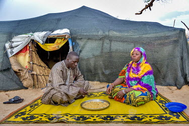 Yakawa Bawa Abacha and her husband eat pasta she cooked on a small fire outside her makeshift shelter. Yakawa Bawa Abacha lives with her five children and her husband in an informal IDP camp in Diffa....