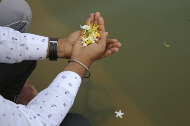 A man holding floral offerings at the Goverdan Radha Kund.