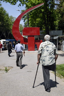 A man on crutches walks towards a red hammer and sickle monument near a bus stop.