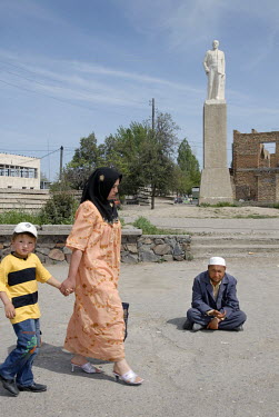A woman and a boy pass a beggar sitting in front of a monument to Lenin.