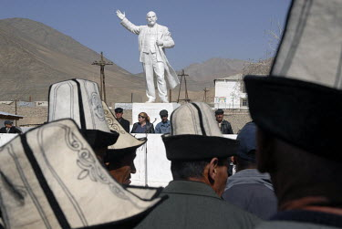 Kyrgyz men wearing traditional hats gather in front of a Lenin monument for the opening speech of a regional youth sports tournament.