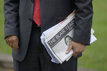 Following Tony Blair's resignation as Prime Minister, a journalist stands on College Green holding a copy of a newspaper which has the headline 'The Blair Years'.  Often referred to as College Green,...
