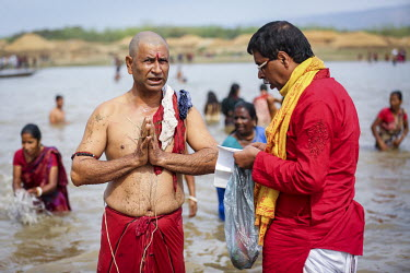 Hindu devotees at the Ganga Sagar Snan mela bathing in the holy water of Ganges River. It is believed that by performing this ritualistic bath, all the sins of the person will be washed away.