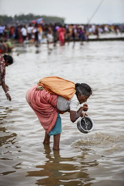A woman drinks water from the Ganges River as Hindu devotees gather to bathe in the holy water of Ganges River during the Ganga Sagar Snan mela. It is believed that by performing this ritualistic bath...