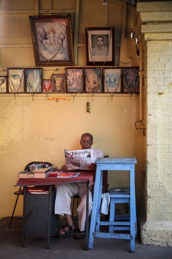 A man reading a copy of The (Kolkata) Telegraph.