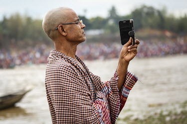 A man takes a 'selfie' photograph as Hindu devotees gather to bathe in the holy water of Ganges River during the Ganga Sagar Snan mela. It is believed that by performing this ritualistic bath, all the...