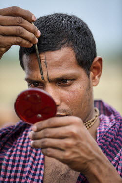 A man makes a 'tilaka' mark on his forehead as Hindu devotees gather to bathe in the holy water of Ganges River during the Ganga Sagar Snan mela. It is believed that by performing this ritualistic bat...
