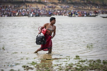 A man walks in the shallows of the Ganges River as Hindu devotees gather to bathe in the holy water of Ganges River during the Ganga Sagar Snan mela. It is believed that by performing this ritualistic...