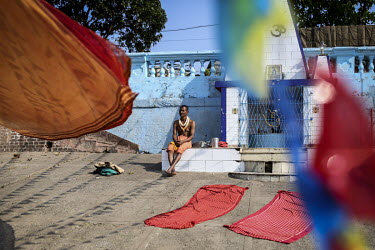 A man sits on the plinth of a shrine beside the Hooghly River.