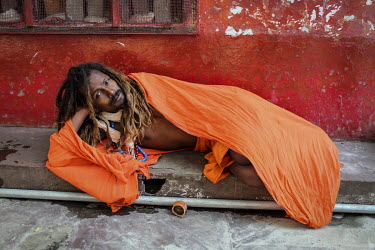 A Sadhu lies on the pavement, wrapped in a safron coloured robe.