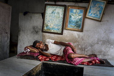 A man sleeps beneath pictures of Hindu deities.