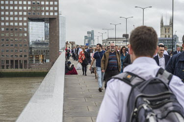 A man begging on London Bridge, crowded with commuters during the morning rushhour.