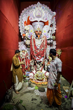 Two men stand in front of a Hindu deity.