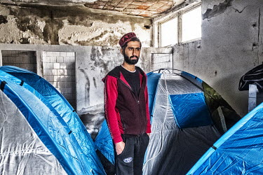 An Afghan refugee standing between tents erected in the former Grafosrem printing factory. He has lived in Antwerp for a number of years but was sent back to Afghanistan but is now trying to get back...