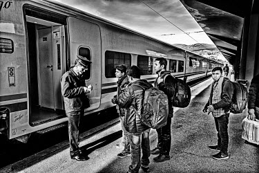 The conductor checks the tickets of a group of Pakistani refugees boarding the Sarajevo-Velika Kladusa train. From Velika Kladusa they hope to cross the Croatian and Slovenian borders on foot into wes...