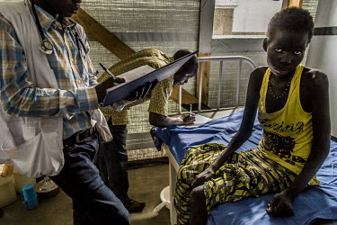 A doctor at a health centre in the Bidibidi Settlement Area examines a young South Sudanese refugee patient, who is HIV positive, suffering from malnutrition and refusing to eat, preferring to let her...