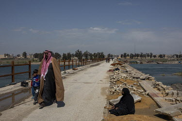 A man and his children pass a woman begging as they walk across a newly repaired bridge that links the southern outskirts of the city to its centre. All bridges spanning the Euphrates river had been s...
