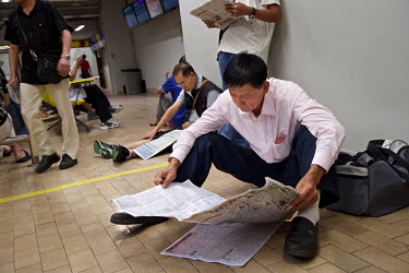 Punters read the sports papers at the Hong Kong Jockey Club's Shatin Racecourse.
