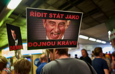 A man carries a placard with a photo of the Czech prime minister Andrej Babis that reads: 'Conduct the country like a dairy cow at a protest which is the biggest political protest since the fall of co...