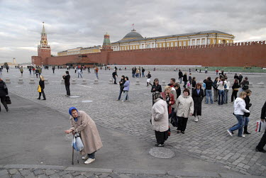 A woman begging in Red Square, with the Kremlin in the background.