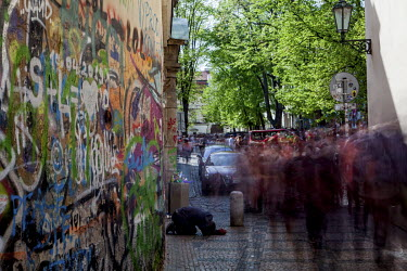 Visitors pass a man begging at the Prague Lennon Wall. Once a normal wall, since the 1980s, it has been filled with John Lennon-inspired graffiti and lyrics from Beatles' songs.