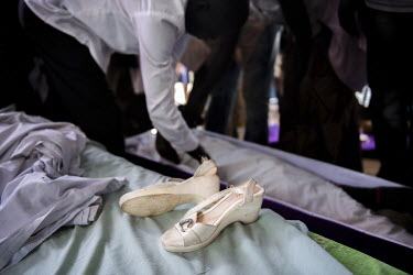 The shoes worn by Lily Ipayi near her swaddled body at her funeral in Bidibidi refugee settlement. She died aged around 42 or 43 having suffered from HIV/AIDS for a deacde. Lily and her family fled to...