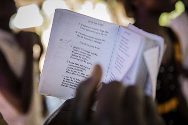 A mourner reads from a bible near the swaddled body of Lily Ipayi at her funeral in Bidibidi refugee settlement. She died aged around 42 or 43 having suffered from HIV/AIDS for a deacde. Lily and her...