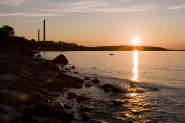 The sunset in Sillamae, a predominantly Russian city on the Gulf of Finland in the north west of Estonia. The 25 metre high hill, in the background, is a waste dump of 25 million tons of uranium, dati...