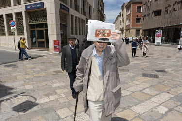 An old man protects his face from the sun with a newspaper while walking along the Via del Corso.