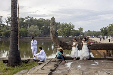 A wedding party take a break from making pictures in the grounds of the Angkor Wat temple complex.