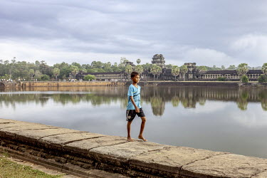 A young boy walks on a wall thta surrounds one of the lakes at the Ankgor Wat temple complex.