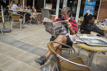 A man reading the Daily Mirror at an out of town shopping 'village'.