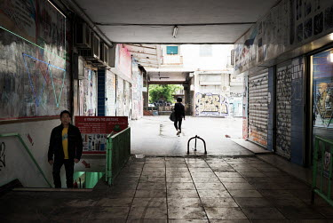 A Chinese man walks up a staircase from a basement shop.