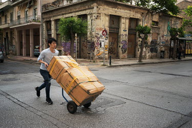 A Chinese porter transports boxes of clothing with a trolley.