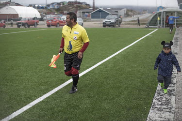 A young fan, and relative of the match officials, runs beside the linesperson during a game. ~~The Greenland soccer league's season lasts less than a week, with its six teams playing five games in as...