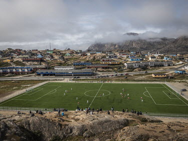 Sisimiut soccer stadium, an artificial pitch surrounded by metal fence between a road and a cliff used as a natural spectator stand.~~The Greenland soccer league's season lasts less than a week, with...