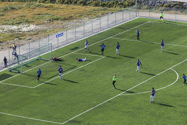 Greenland soccer league team B-67 (blue) score against rivals IT-79 (purple) at the Sisimiut stadium.~~The Greenland soccer league's season lasts less than a week, with its six teams playing five game...