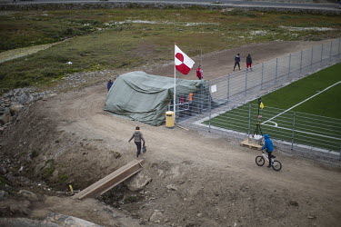 Rough ground surrounding the new pitch reveals what the former tournament was played on, a dirt surface littered with rocks. ~~The Greenland soccer league's season lasts less than a week, with its six...