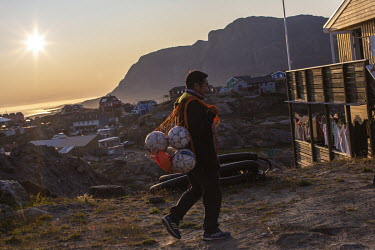 The coach of Greenland football league side G44 walks to the after-game meal carrying soccer balls.~~The Greenland soccer league's season lasts less than a week, with its six teams playing five games...