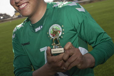 After a game, a player from Greenland football league side N48 holds his man of the match trophy for photographers.~~The Greenland soccer league's season lasts less than a week, with its six teams pla...