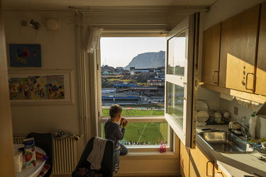 Nikki Jensen (6) watches a Greenland league match from the kitchen in his home that overlooks the sports stadium in Sisimiut. ~~The Greenland soccer league's season lasts less than a week, with its si...