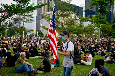 A man holding a USA flag sits among people gathered in front of government buildings in the Admiralty District in order to commemorate the 5th Anniversary of the start of the 2014 'Umbrella Revolution...