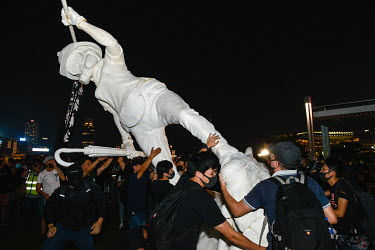 A statue of an umbrella toting protestor is raised in front of government buildings in the Admiralty District during an event to commemorate the 5th Anniversary of the start of the 2014 'Umbrella Revo...