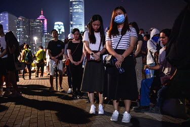 People stand with their heads bowed for a moment of silence during a commemoration of the 5th Anniversary of the start of the 2014 'Umbrella Revolution' in the Admiralty District.