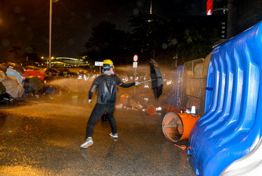 Umbrella wielding protestors close-in on government buildings as police use water canons to disburse them at the end of an event to commemorate the 5th Anniversary of the start of the 2014 'Umbrella R...