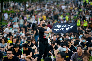 A man waves a black flag as people gathered in front of government buildings in the Admiralty District in order to commemorate the 5th Anniversary of the start of the 2014 'Umbrella Revolution'.